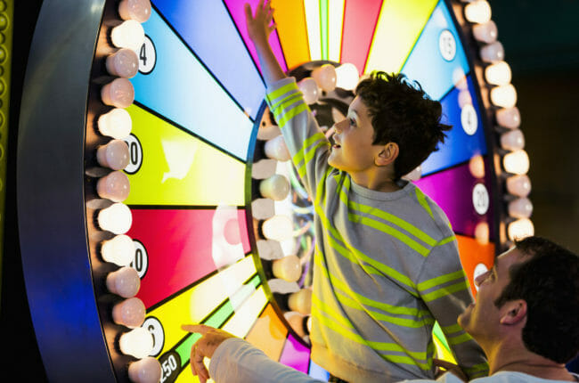 Little boy (5 years, mixed race, Hispanic / Caucasian) with father, spinning a colorful, illuminated wheel at an amusement arcade.